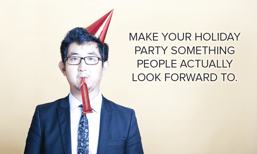 A businessman wearing a party hat with a party favor in his mouth