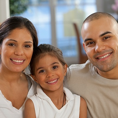 Family Dentistry in Maple, ON - A family of three smiling for the camera. Routine cleanings help prevent bleeding gums, bad breath, and keep your smile healthy.