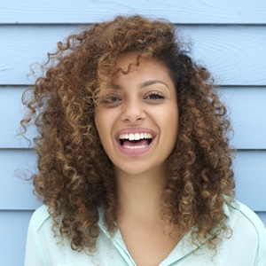 A young woman beaming with a healthy smile thanks to the quality treatments from her dentist in Maple, ON.