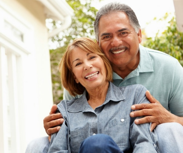 Older couple smiling confidently after restorative dentistry treatments