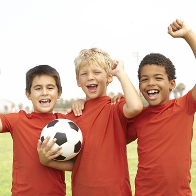 Family Dentistry in Maple, ON - Sportsguards - Thrre little boys on the same soccer team holding a soccer ball and cheering. Keep you or your child's teeth protected while playing sports.