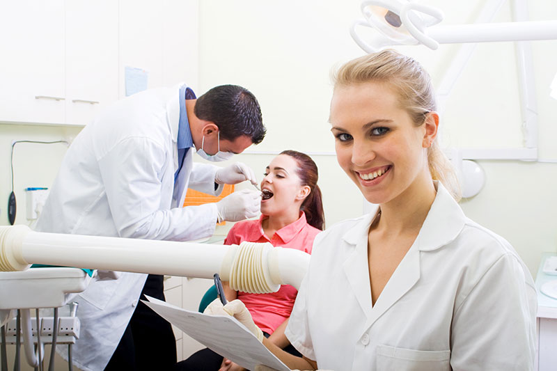 dental assistant looks at camera while doctor works on patient in the background